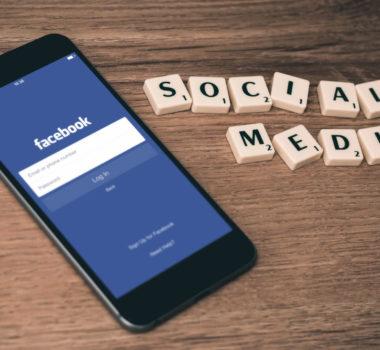 Ekran logowania facebook na telefonie, po lewej napis social media z klocków.