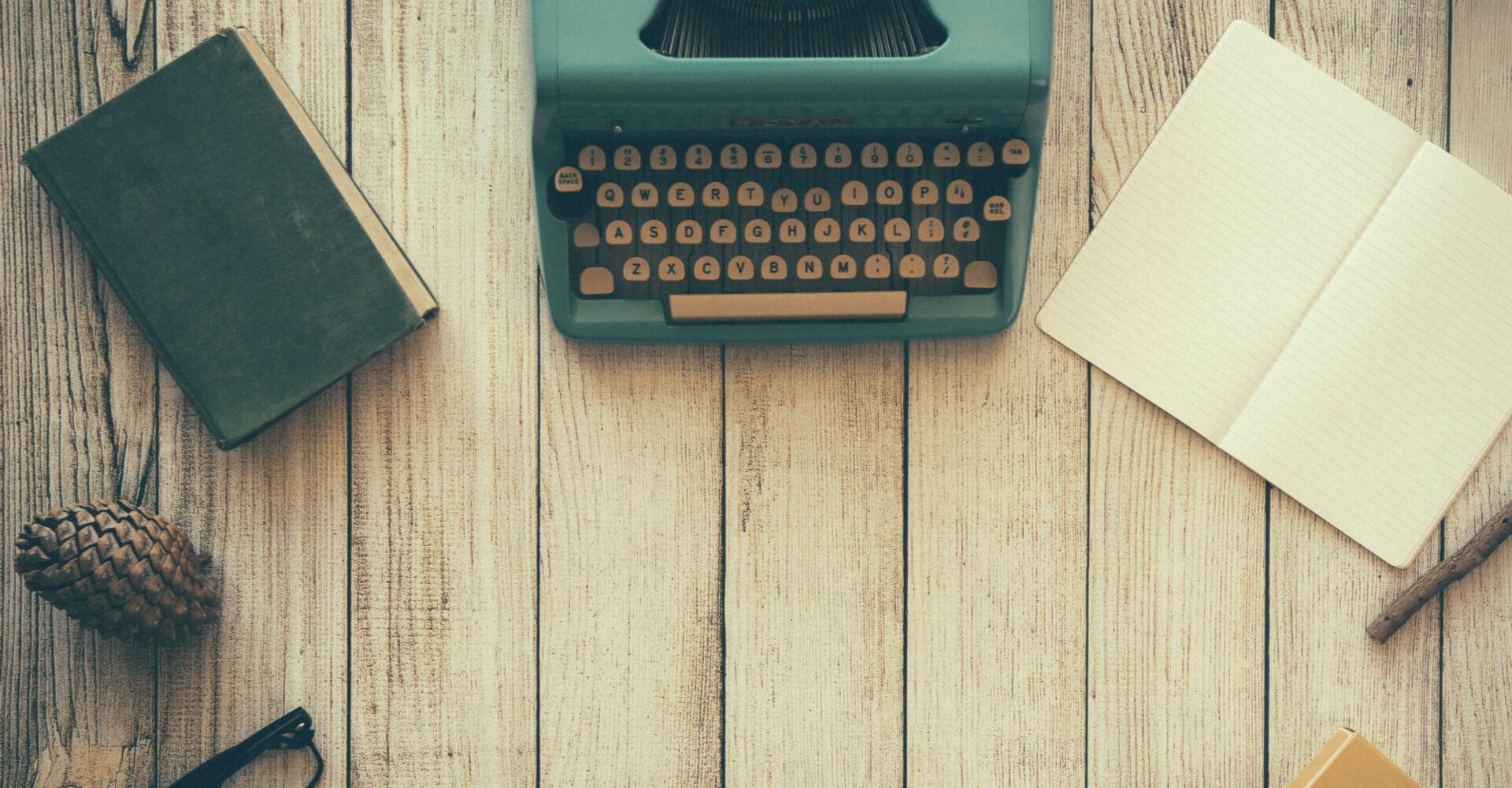 Maszyna do pisania, notatnik i książka na tle z desek.