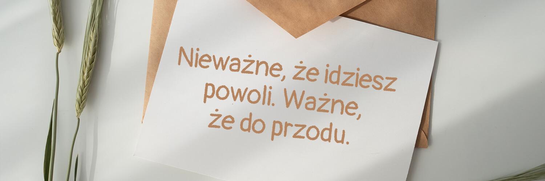 Darmowe fonty odręczne - Pangolin - napis na kartce papieru leżącej na kopercie.